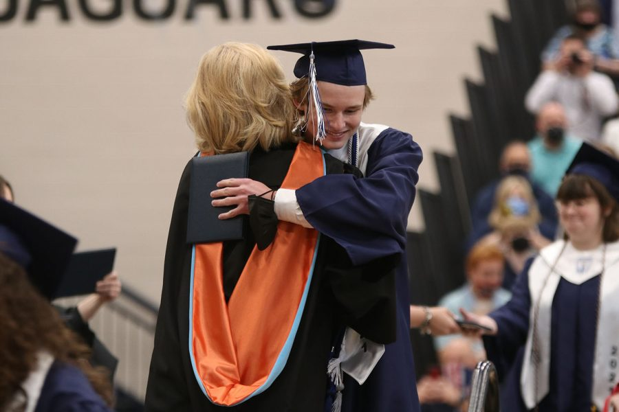After walking across the stage, senior class president Jonathan Atchley hugs principal Dr. Gail Holder.