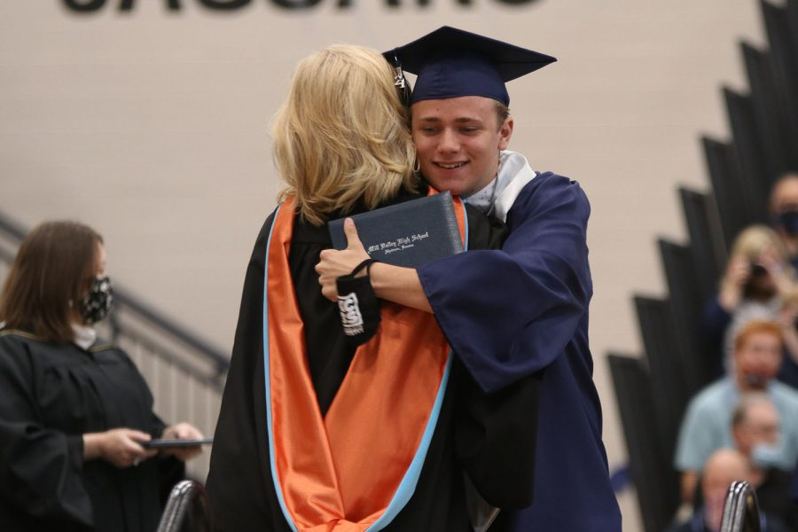 At the end of the stage, senior Noah Collins hugs principal Dr. Gail Holder.
