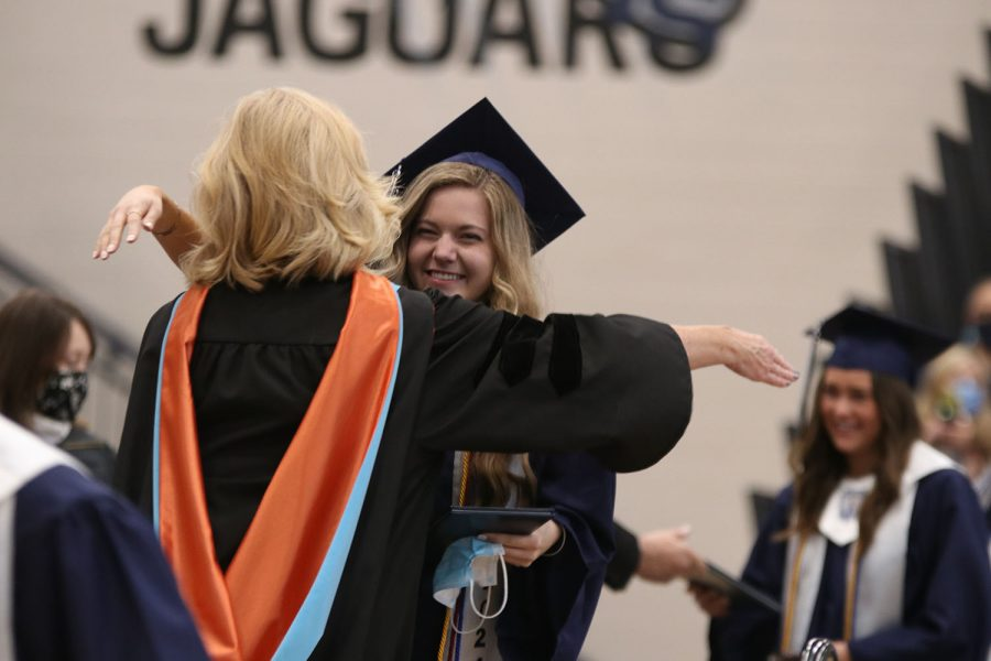 Holding her hands out, senior Emily Feuerborn goes in for a hug with principal Dr. Gail Holder.