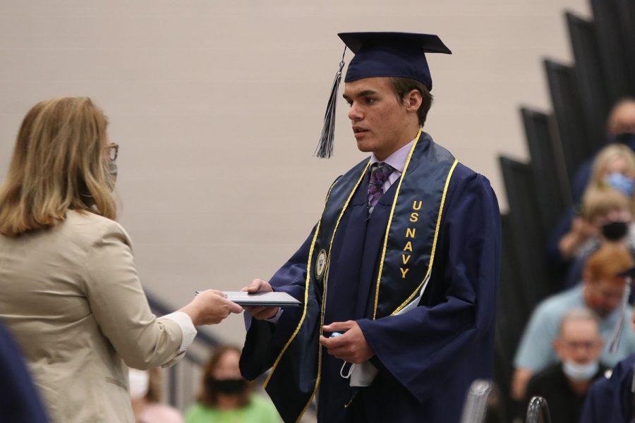 On stage, senior Alec Schmidt receives his diploma.