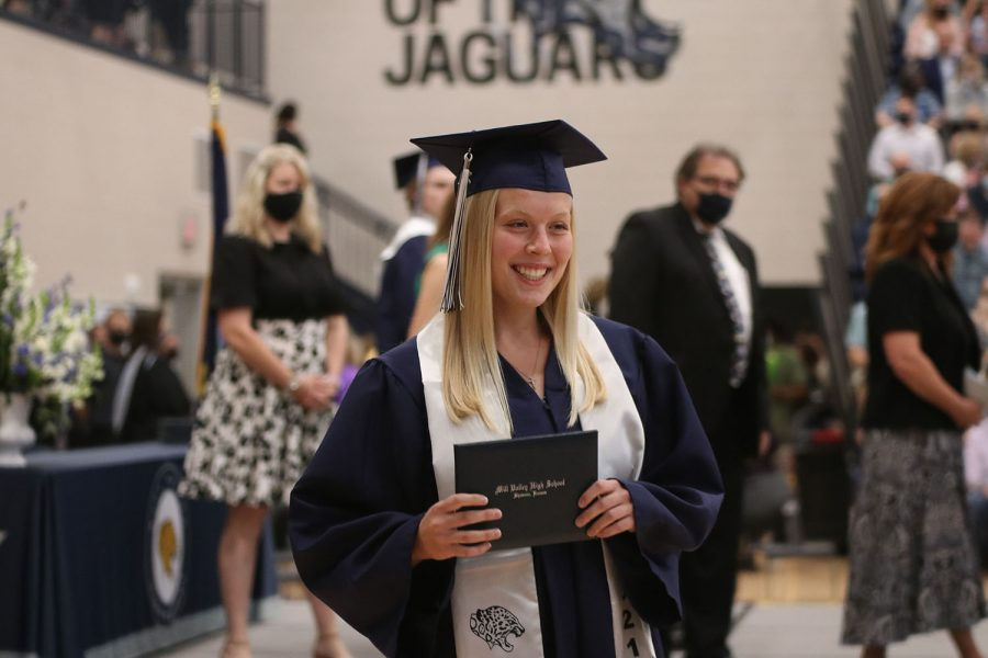 After walking across the stage, senior Elle Zars poses for a picture with her diploma.