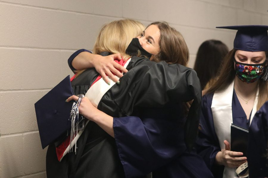 With her cap in one hand, senior Caiden Dean hugs counselor Patricia Chandler.