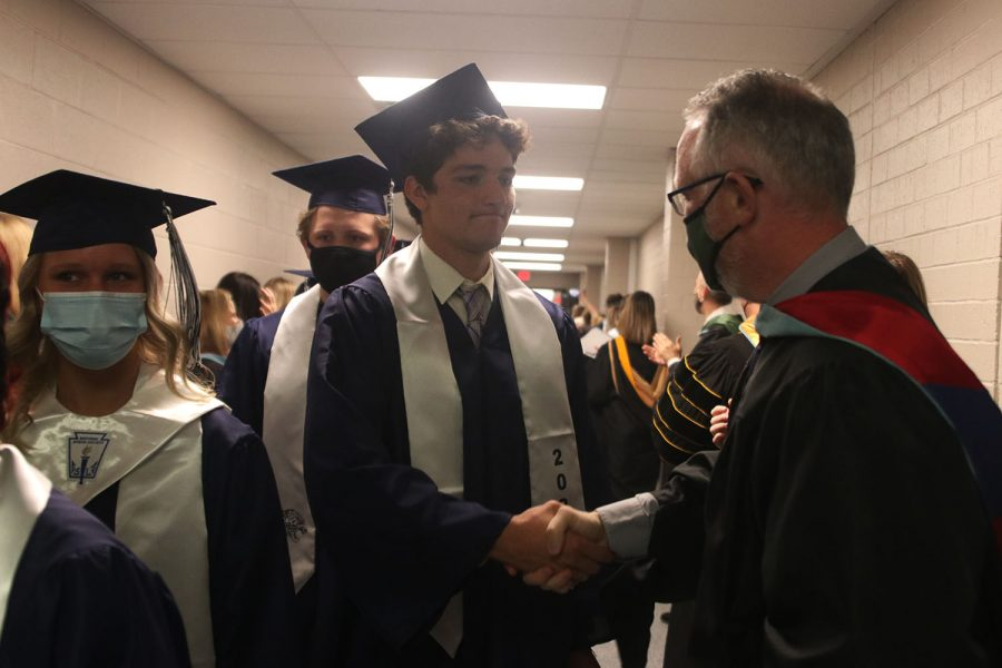 After the ceremony, senior Pete Janssen shakes hands with his previous science teacher Chad Brown.