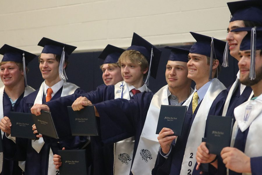 Holding their diplomas out, seniors Colin Maddox, Kyle Moylan, Drew Powers and Andrew Archer smile for a picture amongst their other friends.