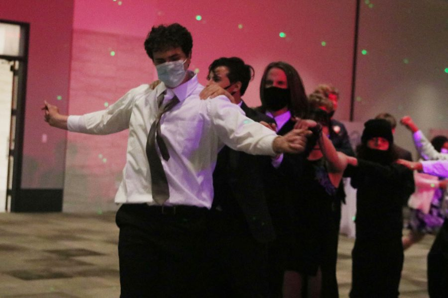 On the dance floor, students participate in a conga line.