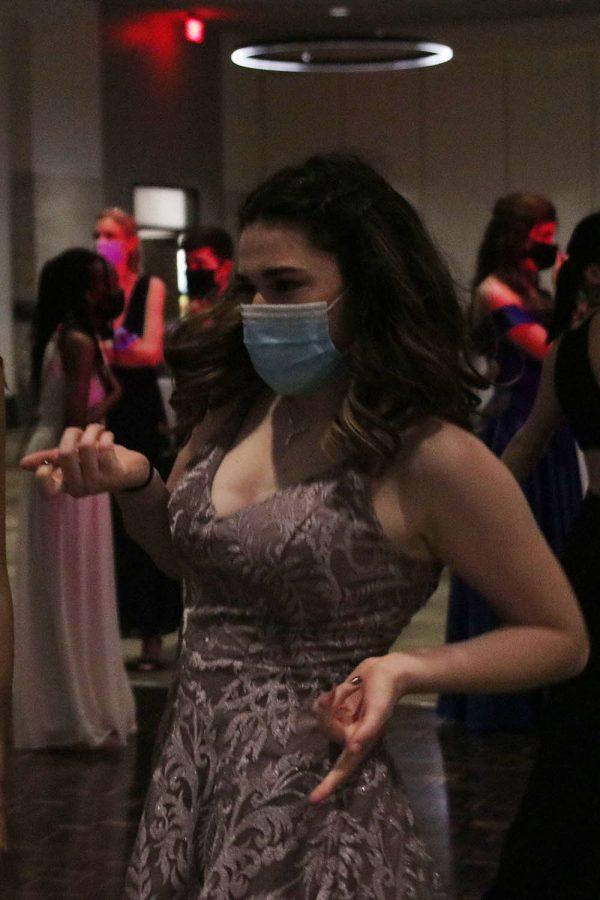 Gesturing her friends closer, junior Kira Tilden continues dancing.