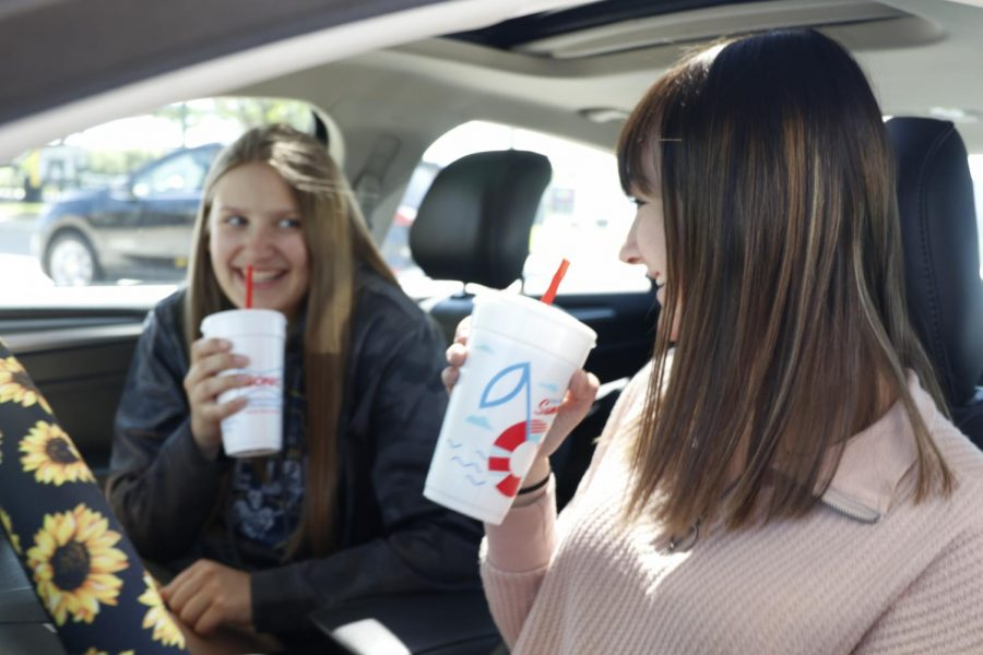 Laughing while conversing about band Thursday, May 6, senior Ella Greenup and freshman Kate Marten get Sonic with one another - an activity they do often together.