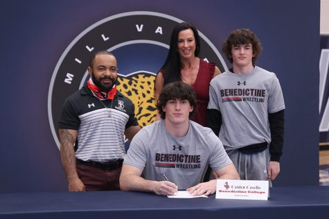 Senior Caiden Casella signs and poses with his parents. Casella will attend Benedictine college for wrestling.