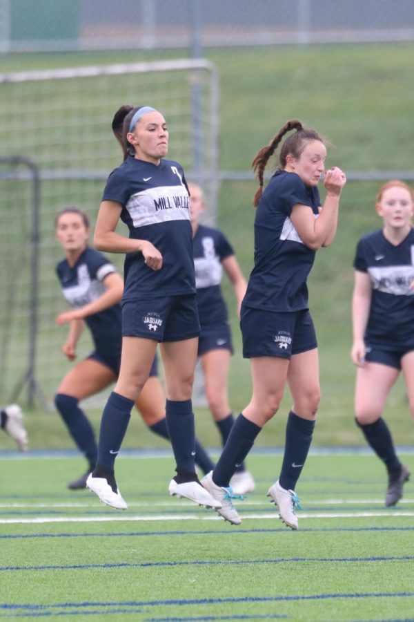 Blocking the ball during a free kick, seniors Katherine Weigel and Hannah Beashore defend the goal.