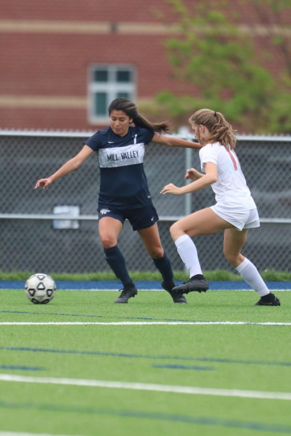 In an effort to defend the ball senior Isabella Loya extends her arm to keep the opponent away from the ball.