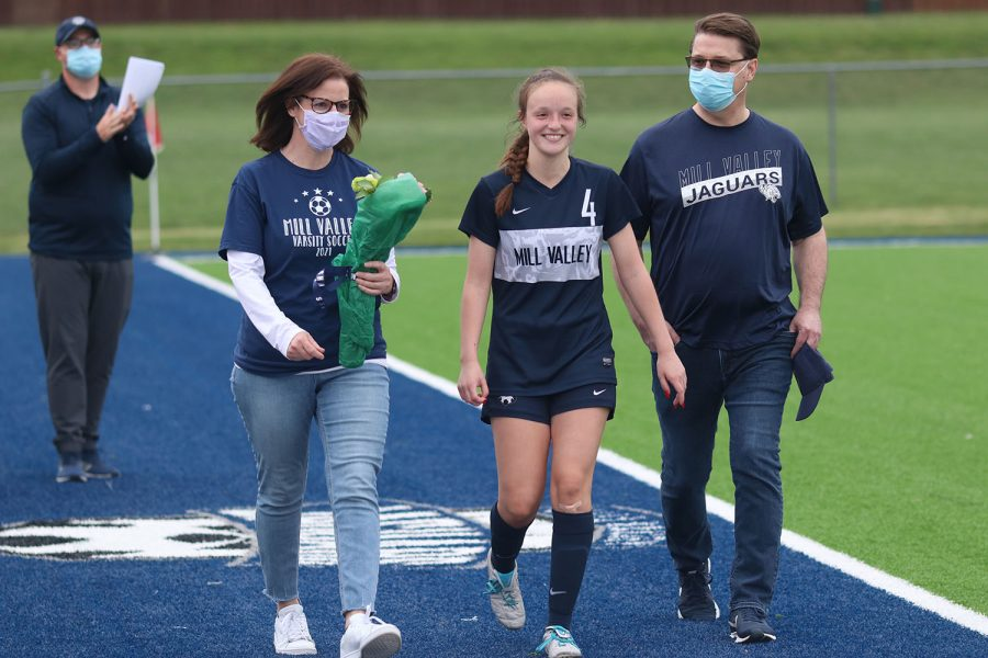 Walking with her parents, senior girls soccer player Hannah Beashore smiles as she approaches the middle of the field.