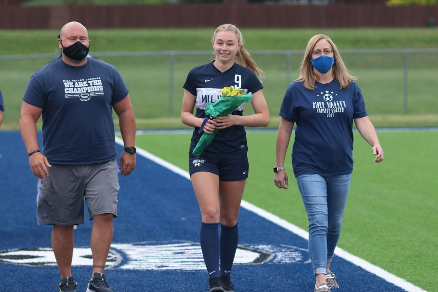 Walking with her parents, senior girls soccer player Mia Colletti holds a bouquet of flowers as she approaches the middle of the field.