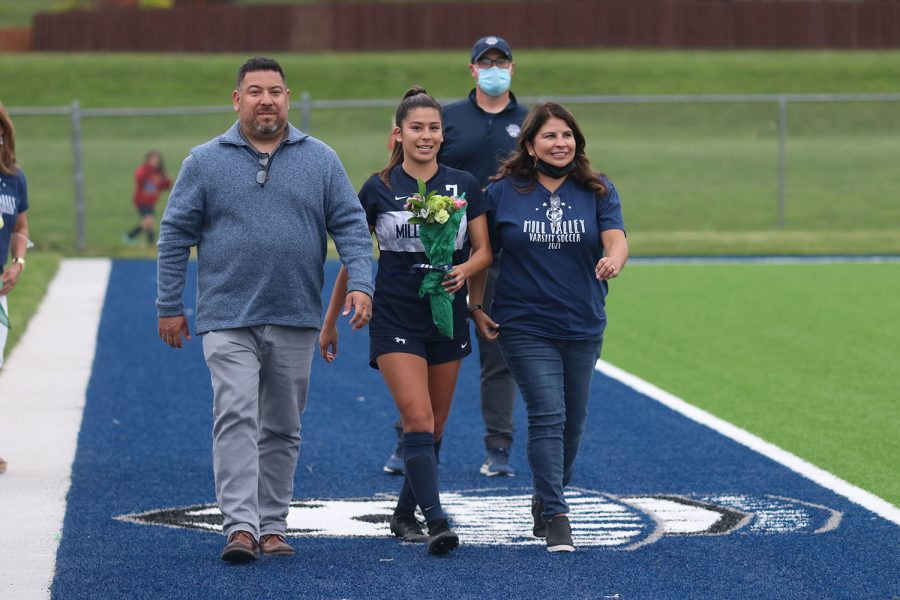 Walking with her parents, senior girls soccer player Isabella Loya holds a bouquet of flowers as she approaches the middle of the field.