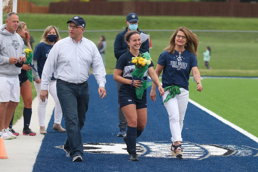 Walking with her parents, senior girls soccer player Avery Norman holds a bouquet of flowers as she approaches the middle of the field.