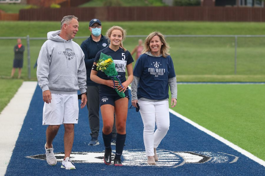 Walking with her parents, senior girls soccer player Molly Ricker holds a bouquet of flowers as she approaches the middle of the field.
