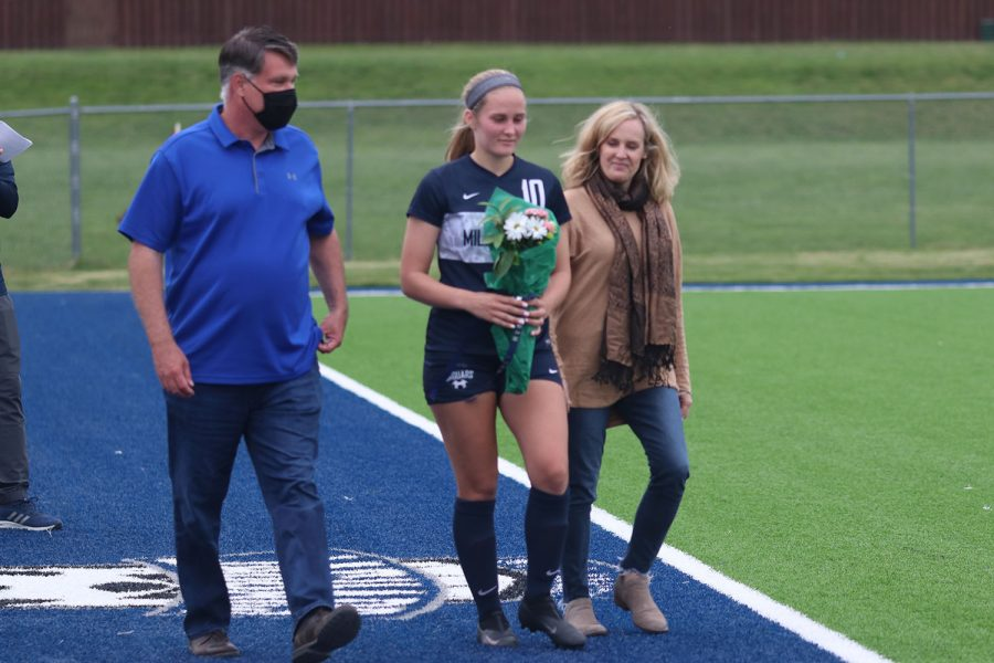 Walking with her parents, senior girls soccer player Emma Schieber holds a bouquet of flowers as she approaches the middle of the field.