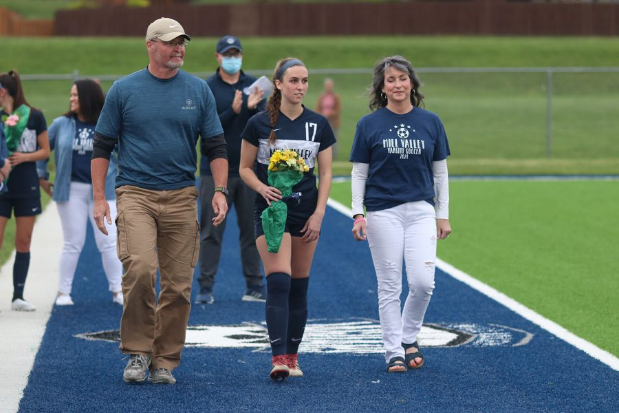 Walking with her parents, senior girls soccer player Katie Turner holds a bouquet of flowers as she approaches the middle of the field.