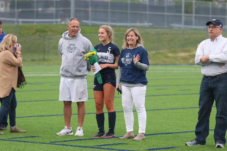 Standing with her parents, senior girls soccer player Molly Ricker holds a bouquet of flowers.