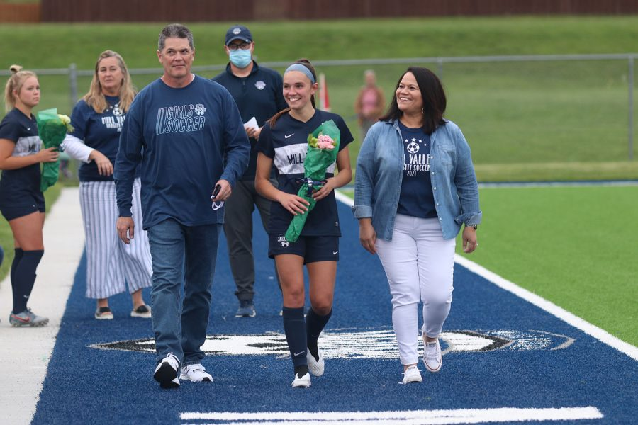 Walking with her parents, senior girls soccer player Peyton Wagoner holds a bouquet of flowers.