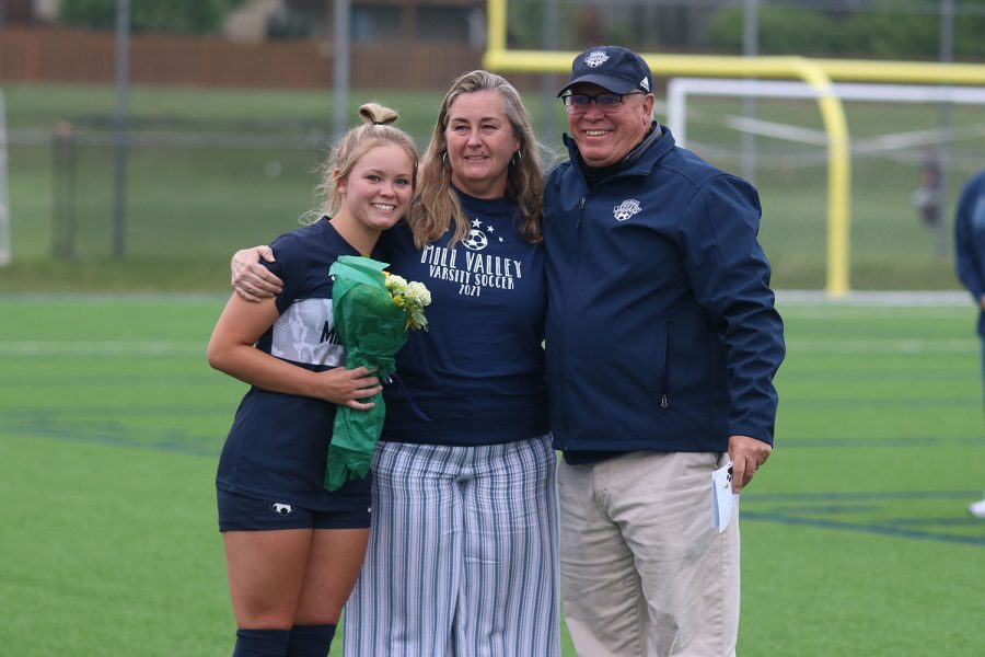 Posing with her parents for a picture, senior girls soccer player Lainey Waldron holds a bouquet of flowers.