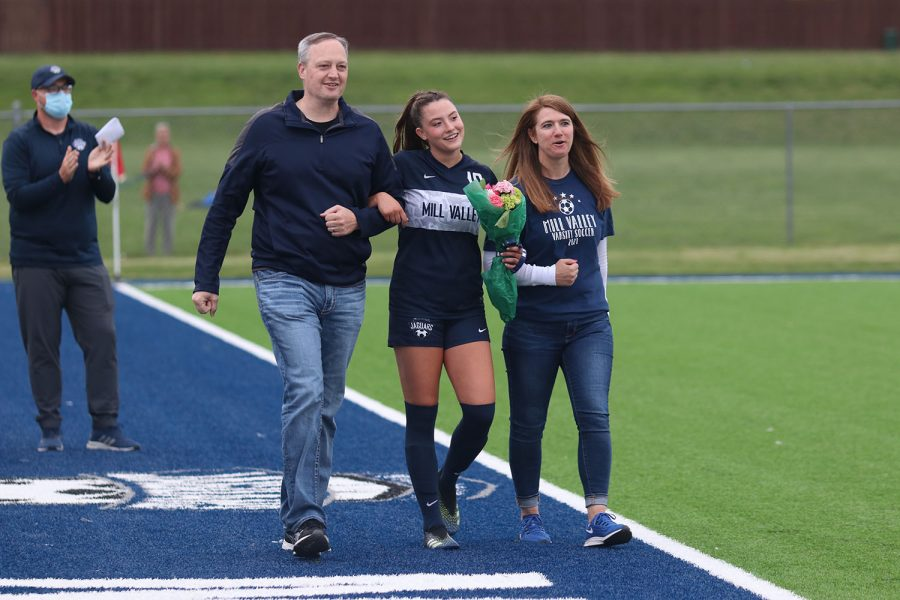 Walking with her parents, senior girls soccer player Katherine Weigel holds a bouquet of flowers as she approaches the middle of the field during girls soccer senior night on Friday, May 7.