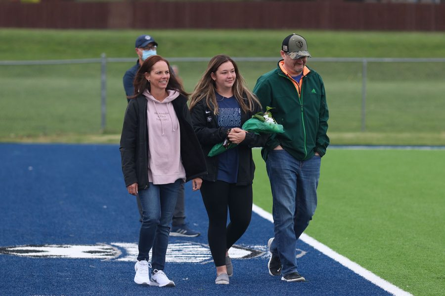 Walking with her parents, senior girls soccer manager Ryleigh Reigle holds a bouquet of flowers as she approaches the middle of the field.