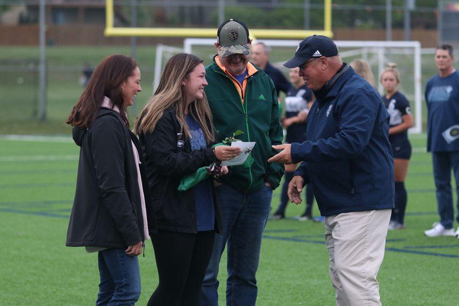 Girls soccer head coach Joe Waldron congratulates senior girls soccer manager Ryleigh Reigle.