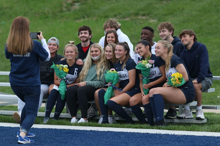 Posing for a photo, senior members of the girls soccer team hold their bouquet of flowers while smiling with their peers during senior night.