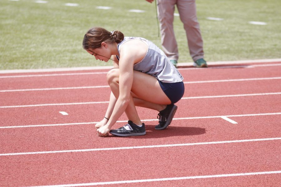 Before the 4x100m relay, senior Lily Fleetwood puts down a piece of tape on the track to label where she will stand to wait for the baton during the race. The girls 4x100m relay team of Fleetwood, senior Peyton Wagoner, junior Kate Roth, and sophomore Savannah Harvey took first place in the relays first heat.