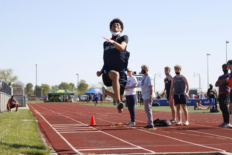 In mid-air, junior Adrien Dimond leaps forward into the long jump pit. Dimond placed 1st in long jump clearing 21-10.50 feet and 1st in triple jump clearing 45-04.50 feet.