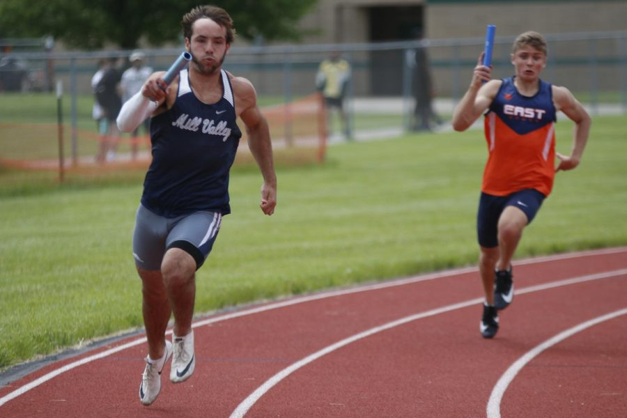 Running the first leg of the 4x100m relay, senior Ty Reishus rounds the curve of the track.