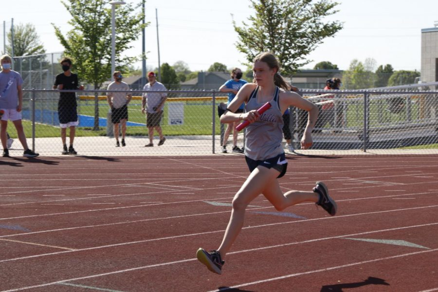 On her second lap, junior Katie Schwartzkopf runs the first leg of the 4x800m relay.