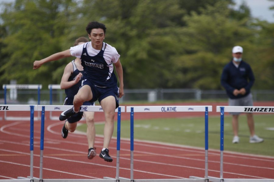 With his arms out, sophomore Dylan Nguyen successfully clears a set of hurdles during the 300m hurdle race. Nguyen took 2nd in the first heat of the race.