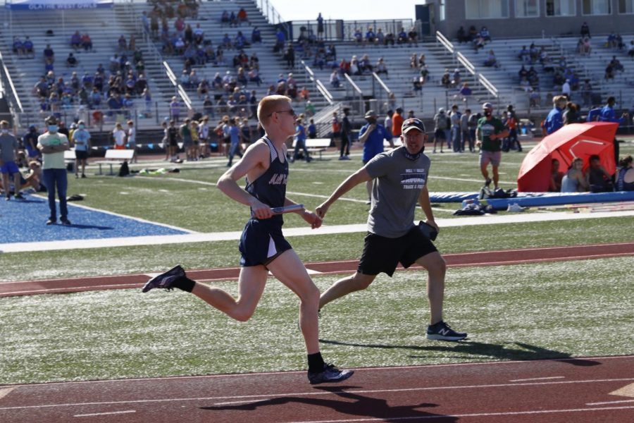 On the sidelines, head coach Chris McAfee yells words of encouragement to senior John Lehan during the boys 4x800m relay.