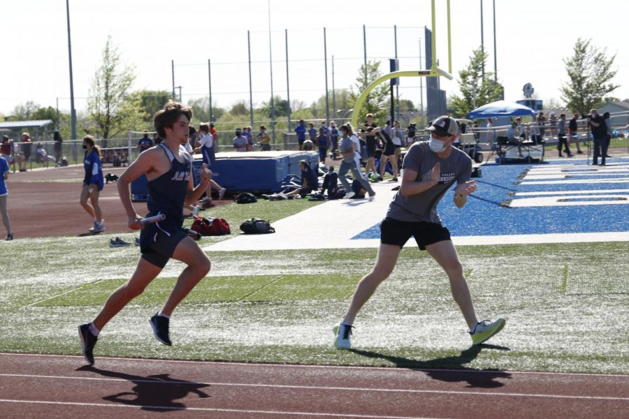 From the infield, distance coach Brian Fitzsimmons cheers on junior Chase Schieber in the 4x800m relay.