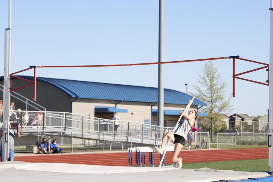 Pole planted, freshman Ava Fleetwood vaults herself over the rope.