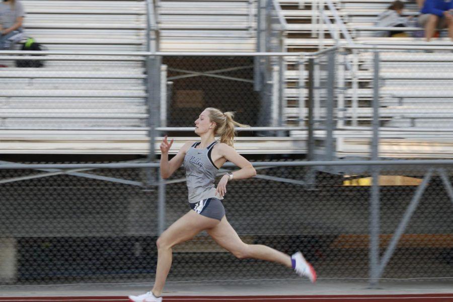Striding out, senior Abby Drumm sprints the 200m dash.