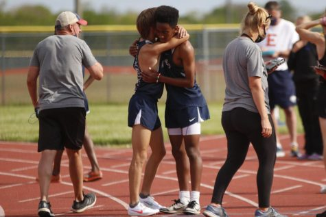 On the track after finishing the 3200m run, freshman AJ Vega and senior Cameron Coad, who placed first and second respectively, share a congratulatory hug.