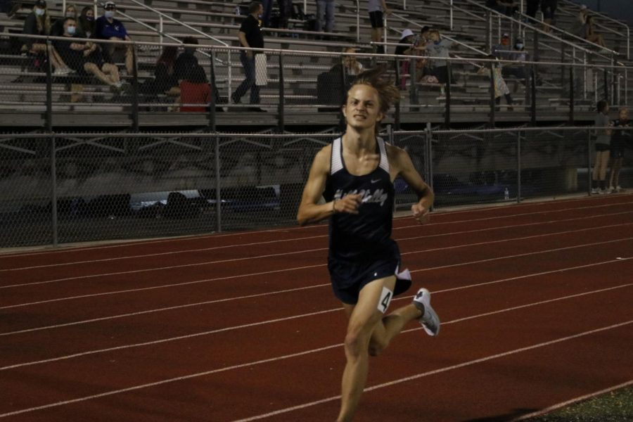 Looking over at the clock, senior Cameron Coad sprints for the final time in the 3200m run. Coad placed 2nd overall running a 9:49 PR.