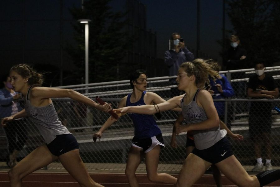 To start the second leg of the 4x400m relay, senior Molly Ricker hands off the baton to junior Reece Johnston. The girls relay team would go on to place 2nd overall running a school record-breaking 4:06.31 4x400m relay.