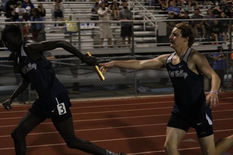 Starting the last leg of the 4x400m relay, junior Kris Twigg passes the baton to sophomore Nen Matlock.