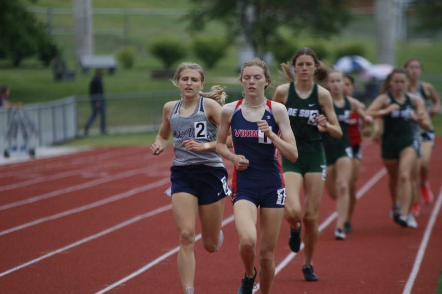 Paying close attention to her opponent, junior Bridget Roy stays on their heels during the 1600m race. Roy finished the race in third place with a time of 5:29.