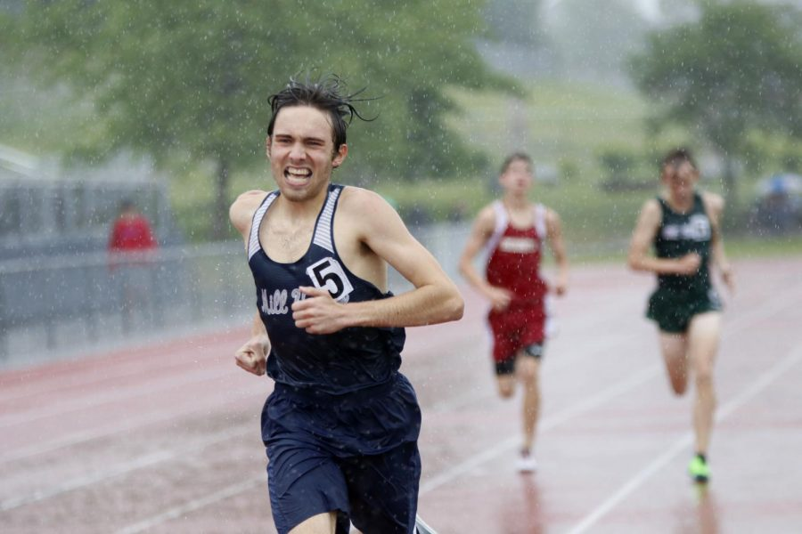 In the torrential downpour, junior Nic Botkin squints through the rain to finish the 1600m race.