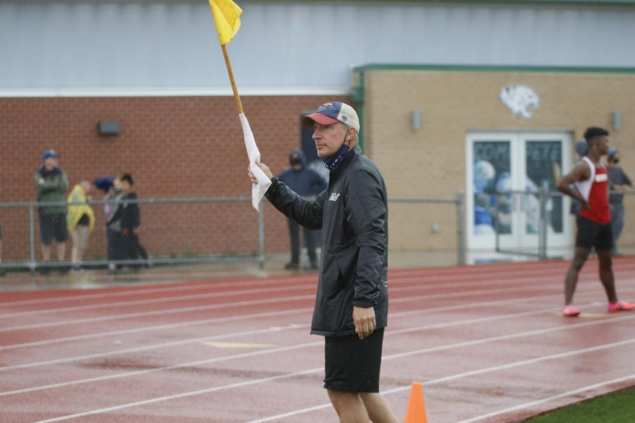 Before the boys 4x100m relay, head track coach Chris McAfee holds up a yellow flag before crossing the track.
