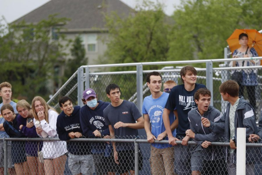 Gathered at the fence, Mill Valley graduates Nathan Greenfield, Matt Turner, Josh Mansfield, Nick Schmidt, Jack Terry, Jenna Walker, Molly Haymaker, and Morgan Koca anxiously watch the end of the boys 800m race.