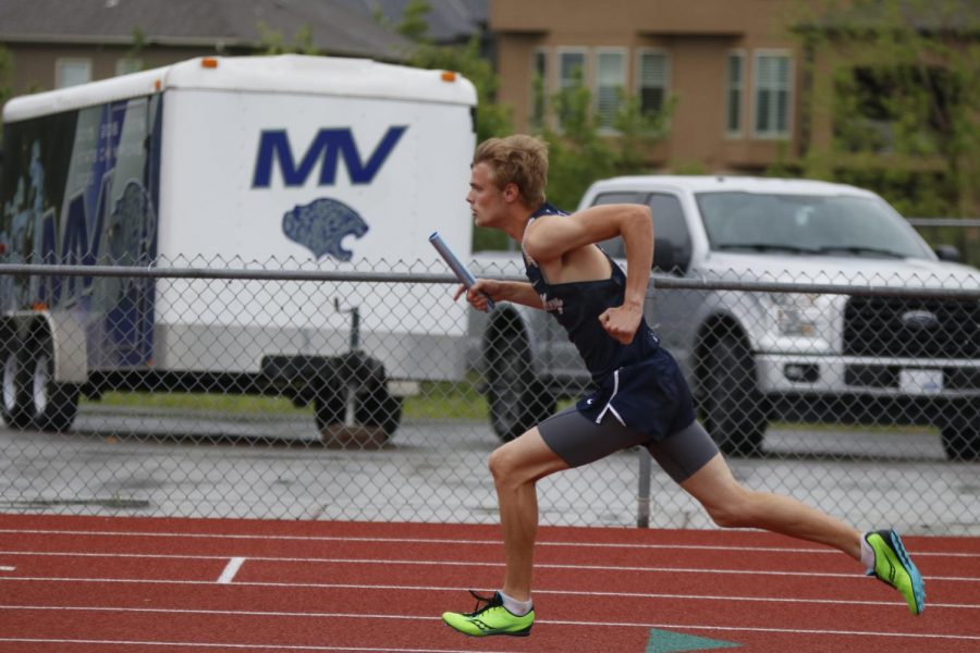 As the first leg of the boys 4x400m relay, senior Leif Campbell pushes off the starting block to start the race.