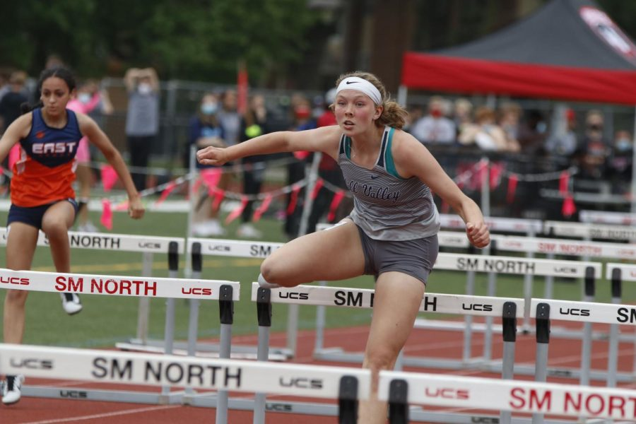 With her arms in the air, junior Emree Zars clears a set of hurdles in the preliminary round of the 100m hurdles. Zars placed 7th in preliminaries and 8th in finals.