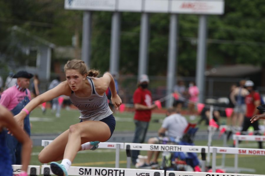 Keeping steady, junior Reece Johnston keeps her arms out to clear the hurdle.