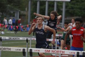 Neck and neck with Bishop Miege, senior Leif Campbell sprints to the next set of hurdles in the 110m hurdle race. Campbell placed 6th in finals with a time of 15.68 seconds.