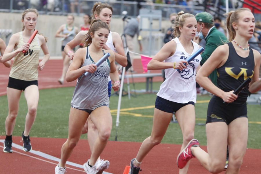 Rounding the first bend of the track with the baton, junior Anna Brazil kicks off the 4x800m relay.